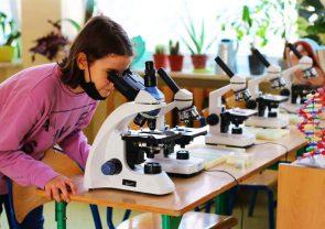 Dziewczynka sprawdza próbkę przez mikroskop
